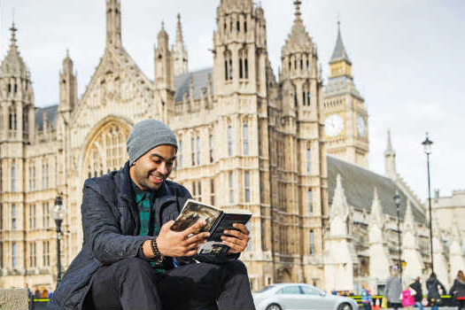 A student sitting outside the UK Parliament